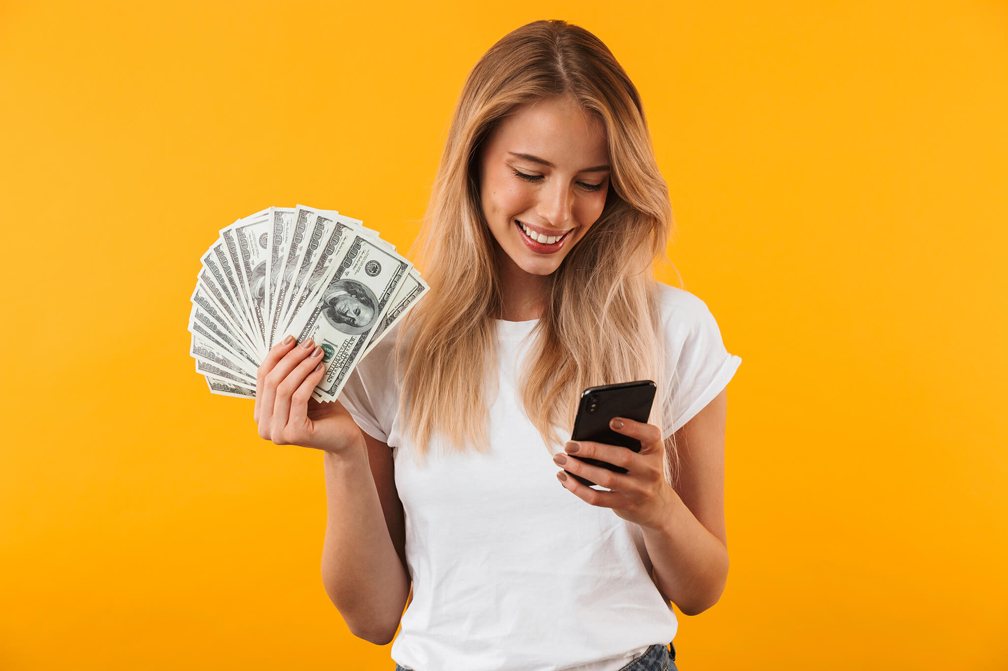 A woman with money in her right hand looking at her smartphone in her left hand